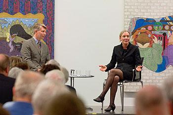 zwei Personen auf dem Podium vor einem Gemälde