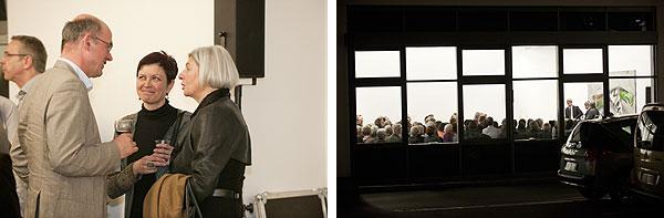 Blick von außen in den Veranstaltungsraum und drei Personen im Gespräch