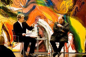 zwei Herren auf dem Podium vor einem Gemälde